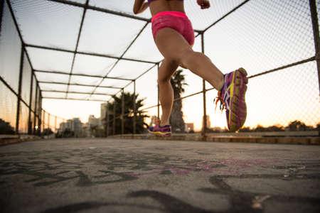 exerting: Legs of female jogger running on walkway