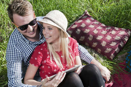 electronic organiser: Young couple sitting on picnic blanket using digital tablet