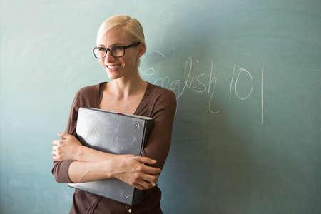 Teacher holding ring binder by blackboard
