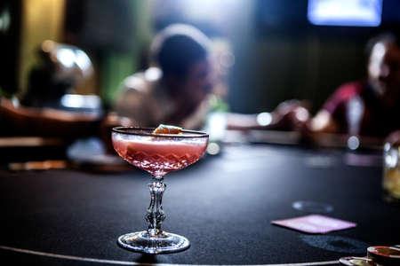 Mediados de los hombres adultos jugando al póquer y beber cócteles