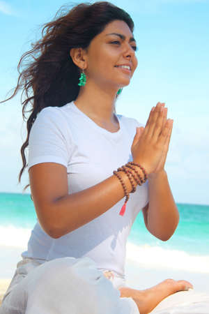 pelo castaño claro: Mujer en posición de loto en la playa, Isla Paraíso, Nassau, Bahamas LANG_EVOIMAGES