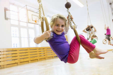 Girl on gymnastic rings in school hall LANG_EVOIMAGES