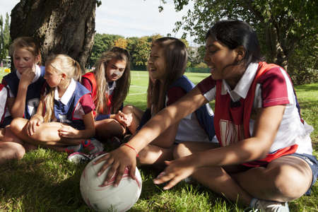low self esteem: Teenage schoolgirl netball team relaxing in break