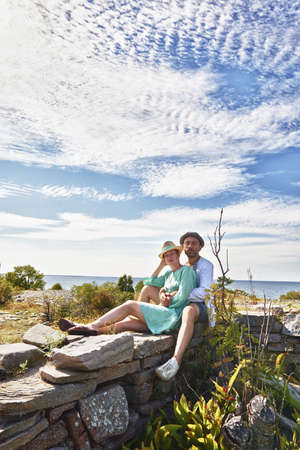 Couple sitting on stone wall,Eggergrund,Sweden LANG_EVOIMAGES