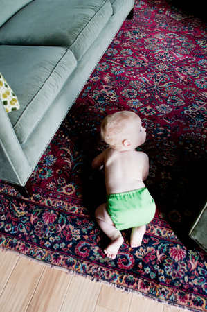 Baby boy crawling on rug, high angle view