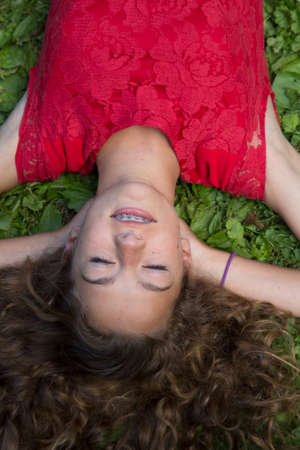 dream land: Close up of teenage girl lying on grass LANG_EVOIMAGES