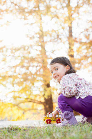 purples: Child with toy car in woods