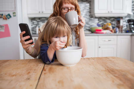 Girl eating breakfast,mother drinking coffee & looking at smartphone LANG_EVOIMAGES