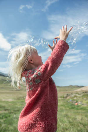 Young girl reaching to catch bubbles LANG_EVOIMAGES