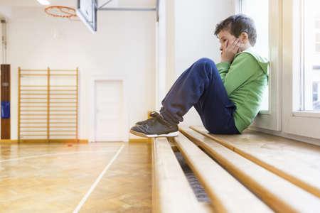 Boy sitting alone on bench in school hall