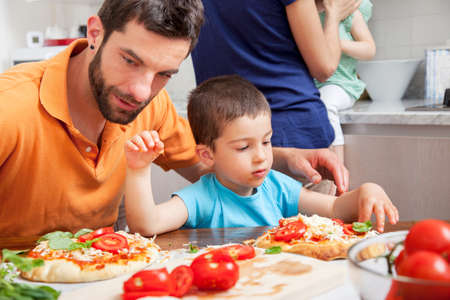Father and son making homemade pizza