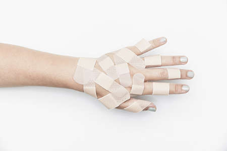recuperating: Cropped hand covered with adhesive plasters