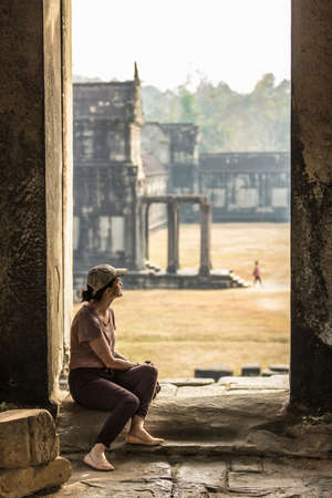 incidental people: Tourist sitting in temple in Angkor Wat,Siem Reap,Cambodia
