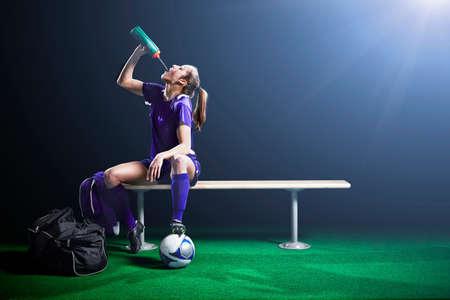strips away: Female soccer player taking a break