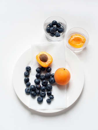 Still life with plate of apricots and blueberries