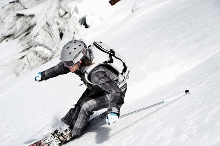 southern european descent: Female skier speeding downhill