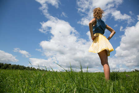 Teenage girl standing with hands on hips in field LANG_EVOIMAGES