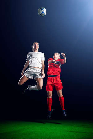 Two female soccer players heading ball LANG_EVOIMAGES