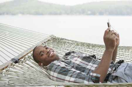 Young man lying on hammock listening to music LANG_EVOIMAGES