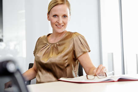 Business woman sitting on office chair,smiling