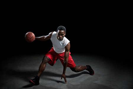 arrodillarse: Studio shot de jugador de baloncesto con pelota