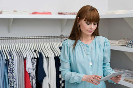 coathangers: Sales assistant in fashion store looking at digital tablet