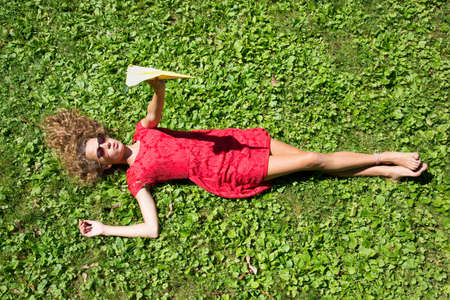 Teenage girl lying on grass holding paper airplane LANG_EVOIMAGES