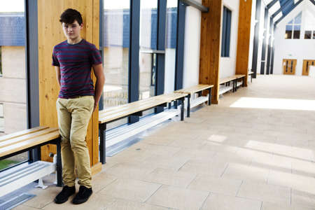 inaccessible: Portrait of isolated teenage schoolboy in corridor LANG_EVOIMAGES
