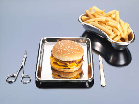 scalpels: Burger and fries sitting in surgical trays illustrating unhealthy diet