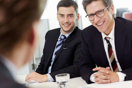 Businessmen sitting around conference table having meeting,smiling LANG_EVOIMAGES
