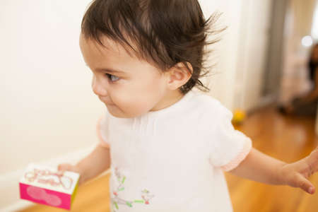 Close up of baby girl with box in hand LANG_EVOIMAGES