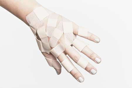 Cropped hand covered with adhesive plasters