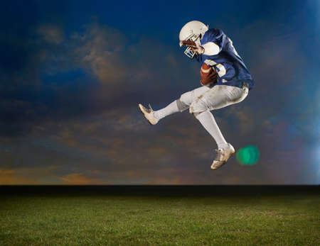 American football player jumping mid air LANG_EVOIMAGES