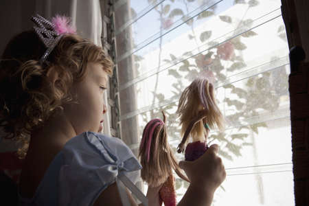 Female toddler looking out of window holding up dolls LANG_EVOIMAGES