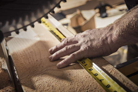 Close up of male carpenter using tape measure in workshop