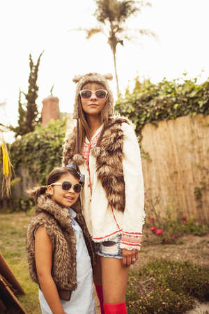 Mother and daughter wearing furry bodywarmers and sunglasses