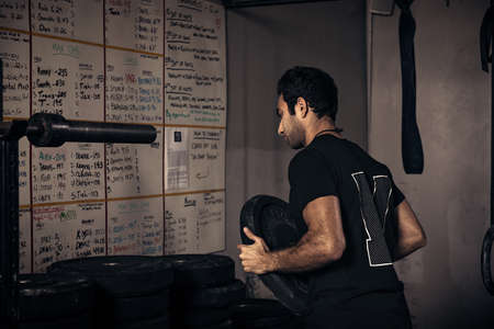 dimly: Fitness instructor arranging weights in gym LANG_EVOIMAGES