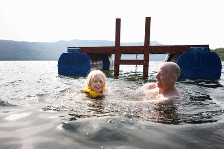 Father and toddler daughter swimming in lake,Silver Bay,New York,USA LANG_EVOIMAGES