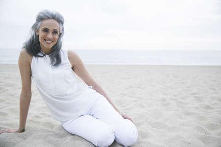 low self esteem: Mature woman relaxing on beach, Los Angeles, California, USA