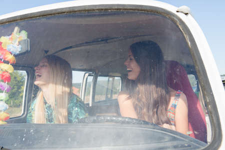 campervan: Young women inside campervan laughing