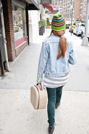 Young woman strolling down street with vanity case