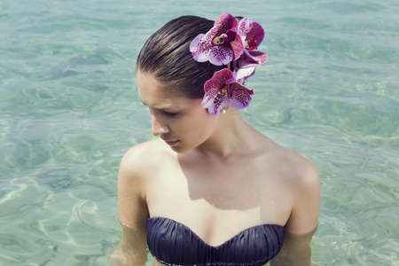 Young woman wearing orchids in her hair wading in lake