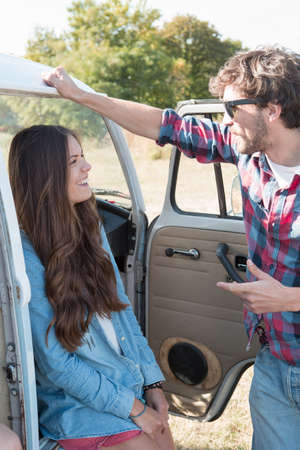 campervan: Young couple talking by campervan