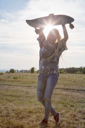 above 18: Young woman holding skateboard above head