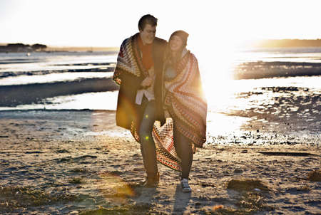 Couple wrapped in a blanket walking on the beach