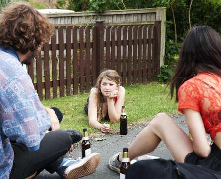 Friends sitting in garden drinking beer
