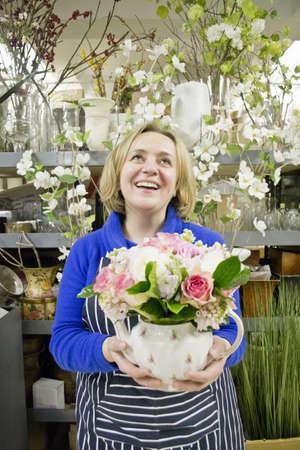 Floral designer holding teapot flower arrangement in studio