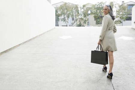 Mature suburban woman carrying shopping bag