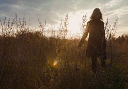 Mid adult woman enjoying country walk at sunset