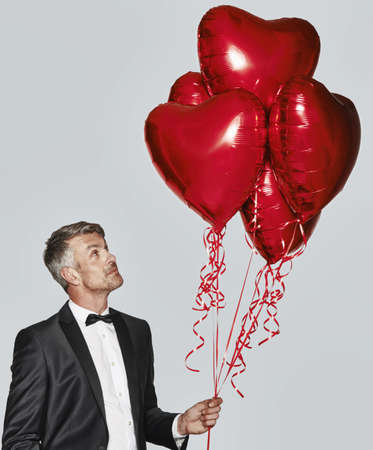 admired: Portrait of man in tuxedo with heart-shaped balloons
